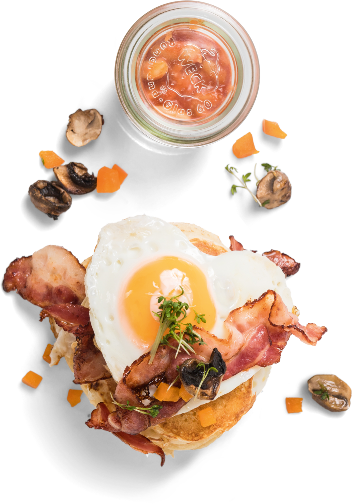 heart-shaped fried egg on pancakes with bacon and baked beans in a small jar
