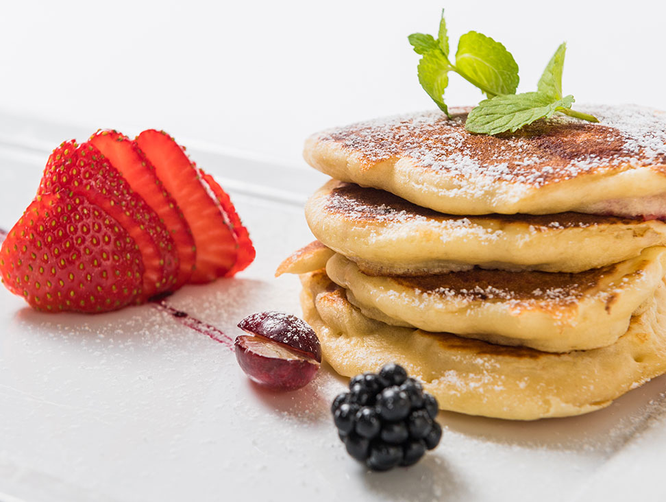 Pancakes with icing sugar and fresh fruits